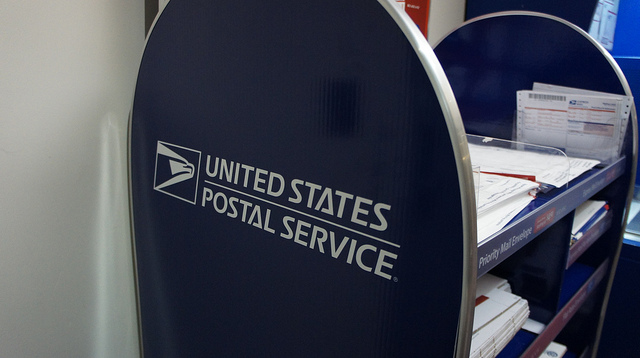 USPS logo on packaging display, APC in background